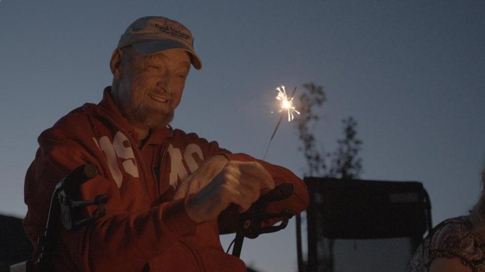 Assis dans un fauteuil roulant et coiffé d'une casquette portant son nom, Paul Vachon tient un feu de Bengale.