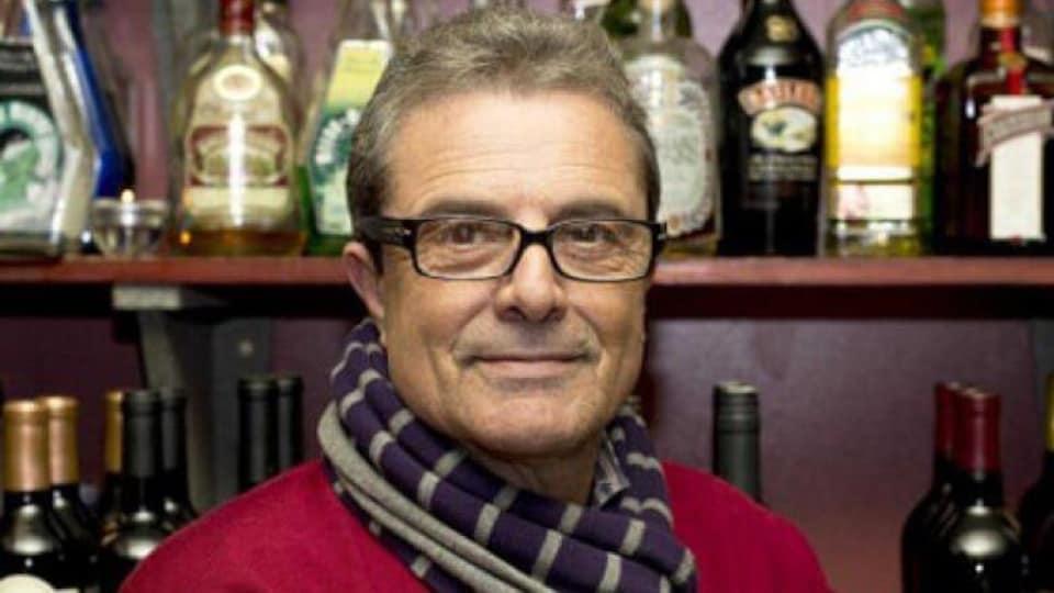 Photo d'un homme portant une écharpe et un pull rouge devant des bouteilles de vin, dans un restaurant.