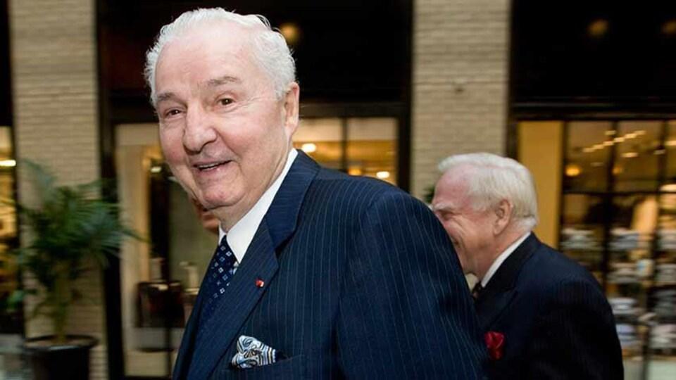 Paul Desmarais en compagnie de deux autres hommes au Centre de commerce mondial de Montréal.