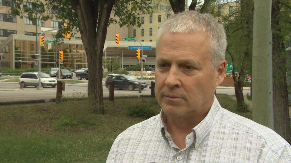 Un homme aux cheveux gris court et chemise blanche rayée, dans un parc, devant un hôpital, l'air sérieux.