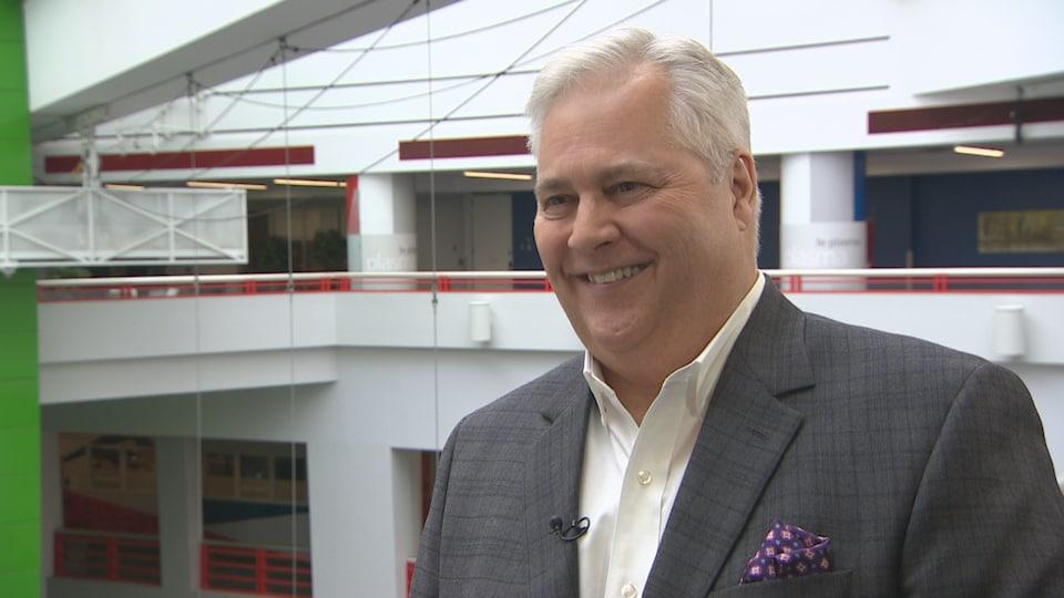 Paul Dubé répond au question de la journaliste devant l'atrium de Radio-Canada.