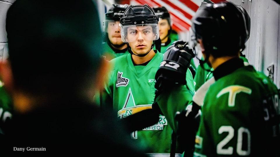 Les joueurs de hockey des Foreurs de Val D'or sont alignés en rang. Ils attendent d'embarquer sur la glace pour leur match.