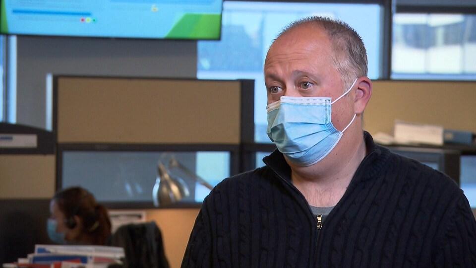 Paul Fortugno portant un masque dans le centre d'appels.