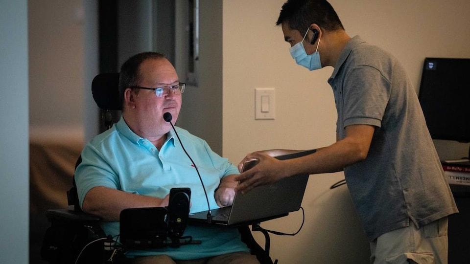 Paul Gauthier, en fauteuil roulant, avec un infirmier.