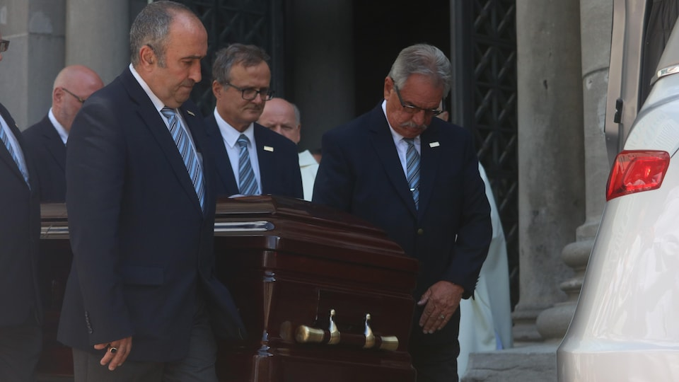 Des hommes portant des vestons et des cravates transportent un cercueil en bois à l'intérieur d'un véhicule à la sortie de la basilique-cathédrale.