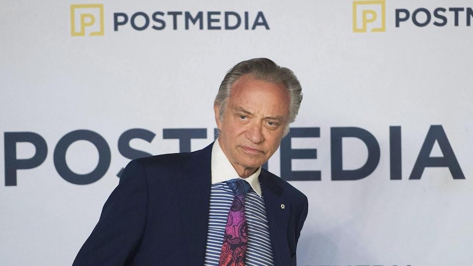 Paul Godfrey en complet pris en photo devant le logo de Postmedia.