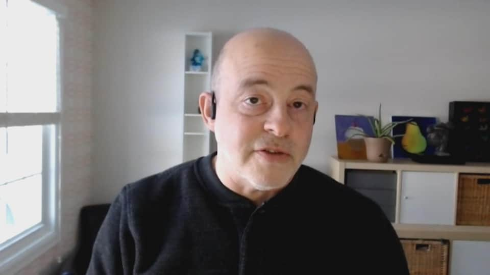 Un homme qui parle devant une caméra Zoom