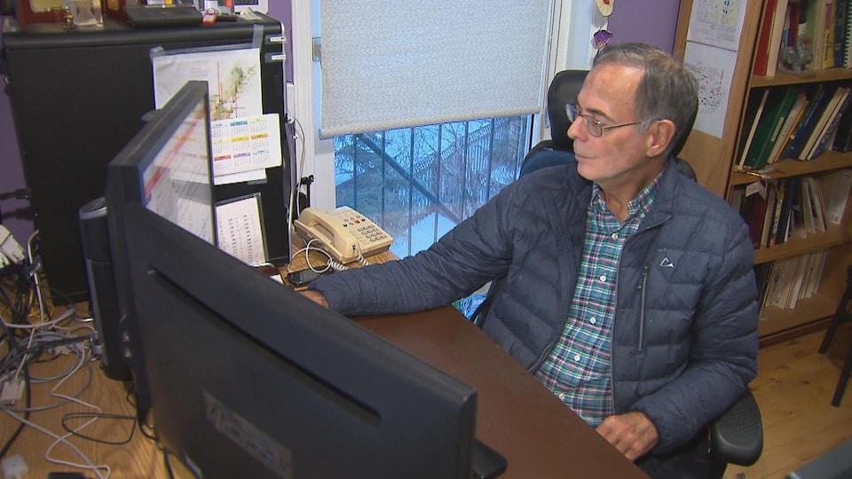 Un homme travaille assis à l'ordinateur.