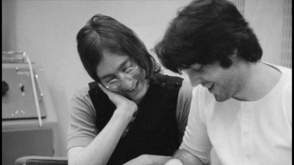John Lennon est assis à côté de Paul McCartney, qui écrit.