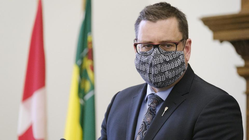 Paul Merriman, portant son masque, lors d'une conférence de presse.