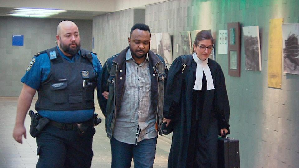 Paul Mukendi est menotté et escorté par un policier ainsi que par son avocate.