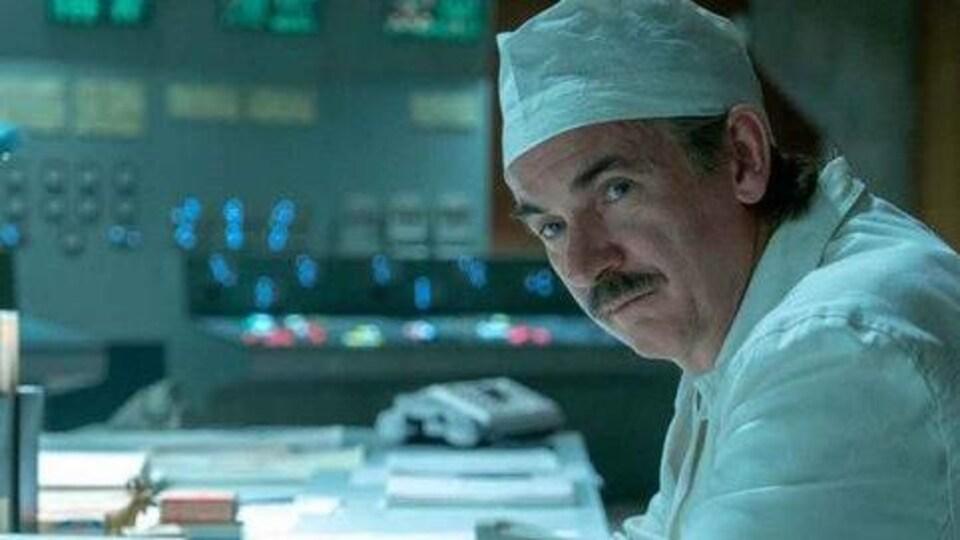 Un homme, assis, portant un sarrau blanc et un bonnet chirurgical.