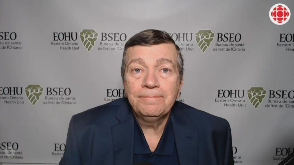 Paul Roumeliotis devant un fond blanc sur lequel on retrouve plusieurs fois le logo du Bureau de santé de l'est de l'Ontario.