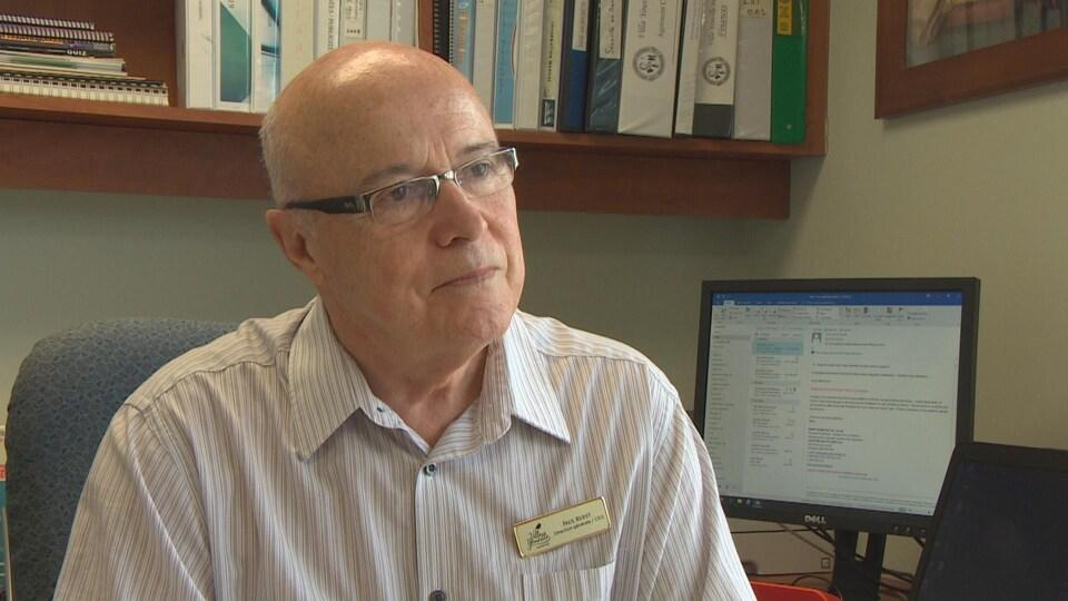 Un homme en chemise blanche porte des lunettes assis dans un bureau.