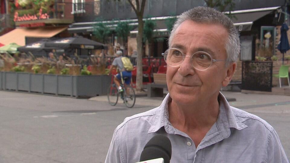 Un homme en train de répondre à des questions, un micro près du visage dans la rue.