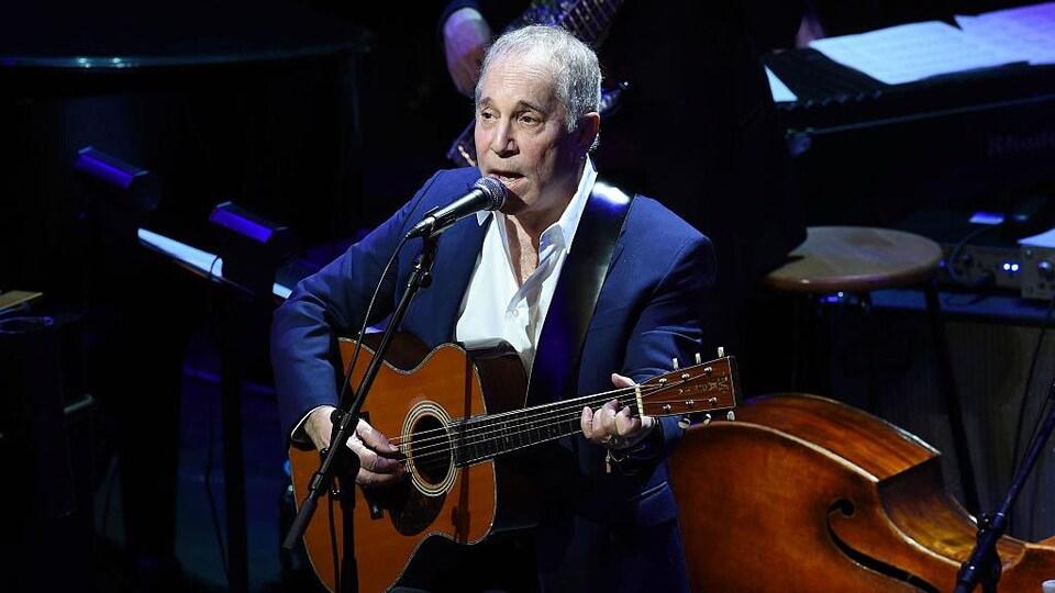 Paul Simon porte un costume bleu et tient une guitare sur scène.