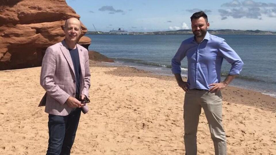 Paul St-Pierre Plamondon et Joël Arseneau sont sur une plage avec une falaise érodée à l'arrière.