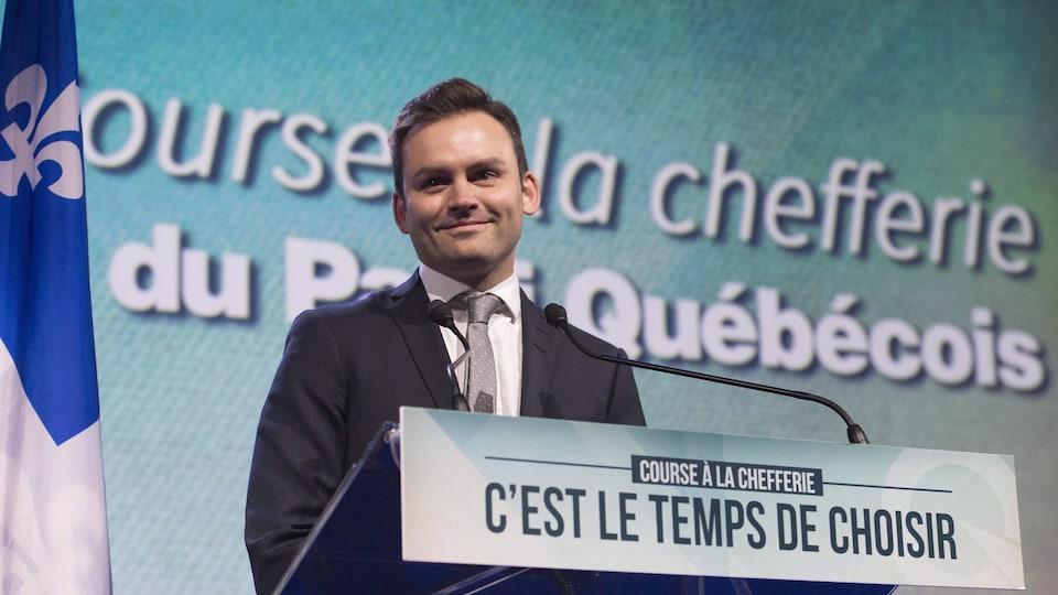 Paul St-Pierre-Plamondon debout derrière un lutrin devant une affiche du Parti québécois.