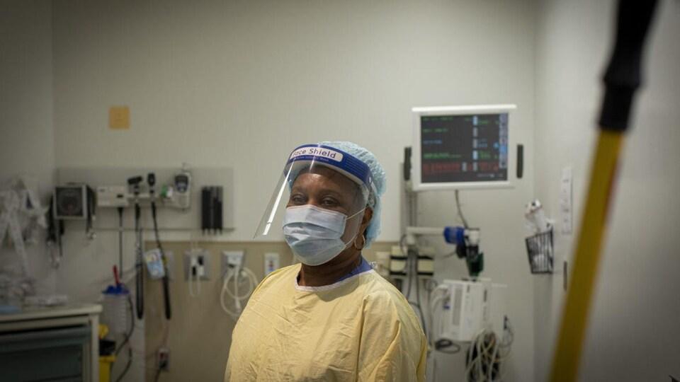 Une femme en blouse, visière et masque dans une chambre d'hôpital