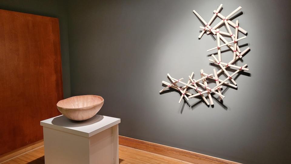 Les rouleaux de céramique sont fixés au mur, alors que le bol aux nuances de beige est exposé sur un socle blanc.