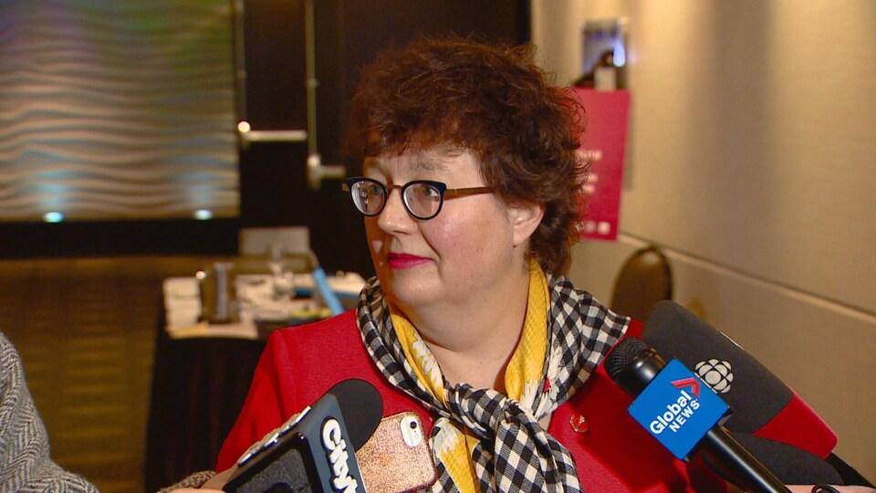 La sénatrice lors d'une conférence de presse, plusieurs micros sont brandis devant elle,