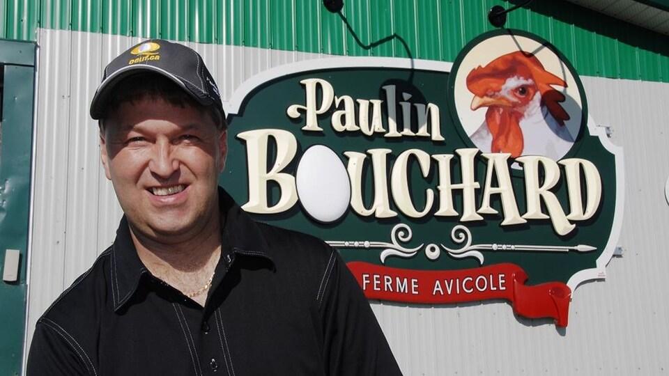Paulin Bouchard devant le logo de sa ferme qui porte son nom.