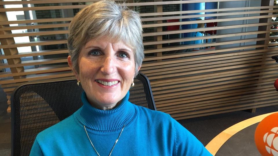 Une femme souriante aux cheveux courts porte un col roulé et une chaîne et des petites boucles d'oreilles.