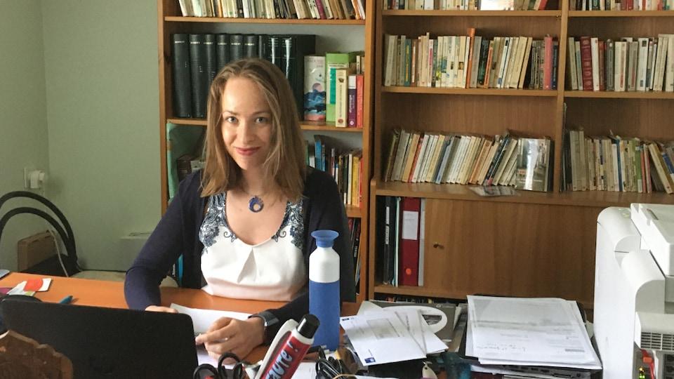 Une jeune femme assise à son bureau.