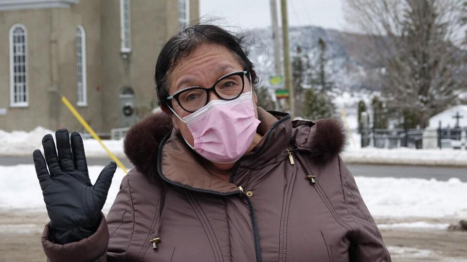 Une dame, qui porte un masque rose, salue de la main.