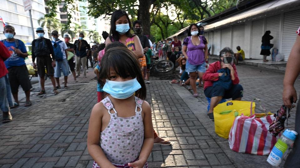 Des gens, dont une fillette, font la file sur le trottoir.
