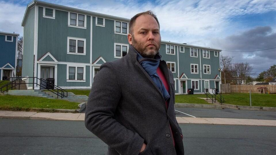 Doug Pawson devant des logements modestes.