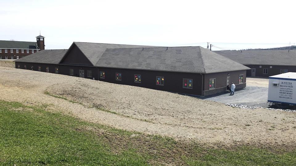 Le bâtiment du foyer de soins vu de loin. Un homme en sarrau blanc est dehors sur le côté de l'édifice.