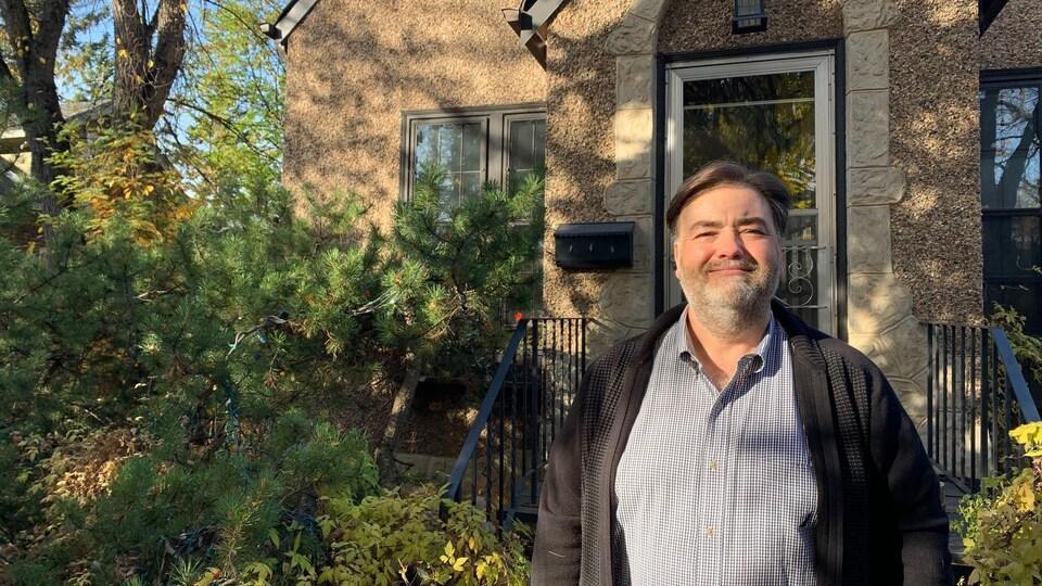 Paul Cote pose devant sa maison.