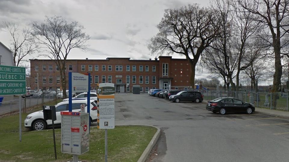 L'édifice est visible à partir de la rue. On voit un stationnement en premier plan.