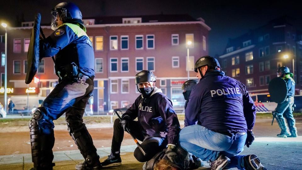 Des policiers arrêtent un homme.