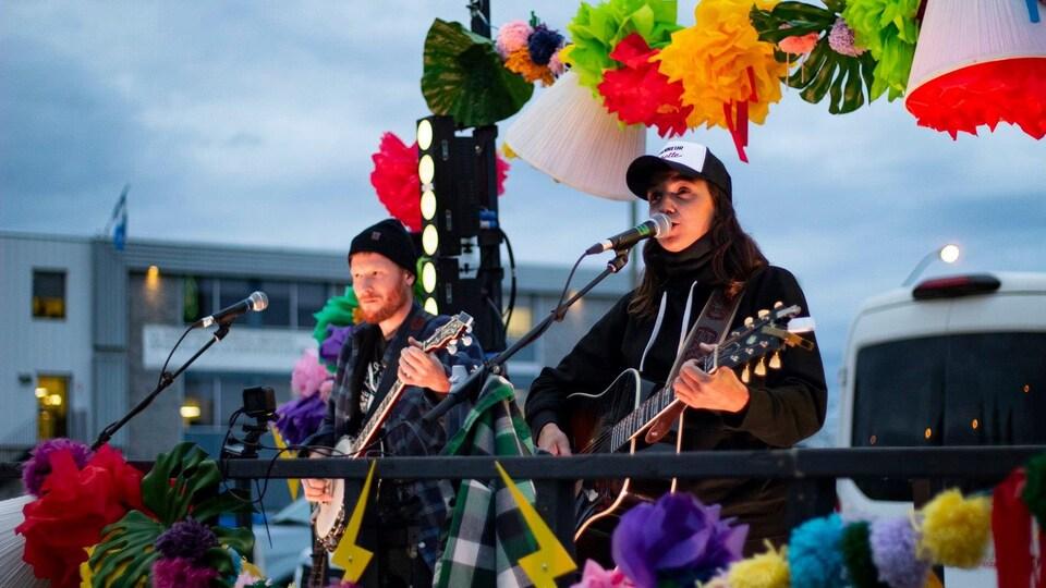 Sara Dufour et un musicien chantent dans une remorque décorée aux couleurs festives.
