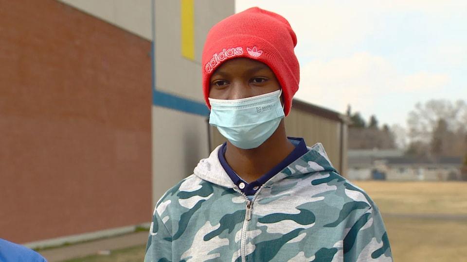 L'élève de 14 ans se tient debout dans la cour de récréation de son école.