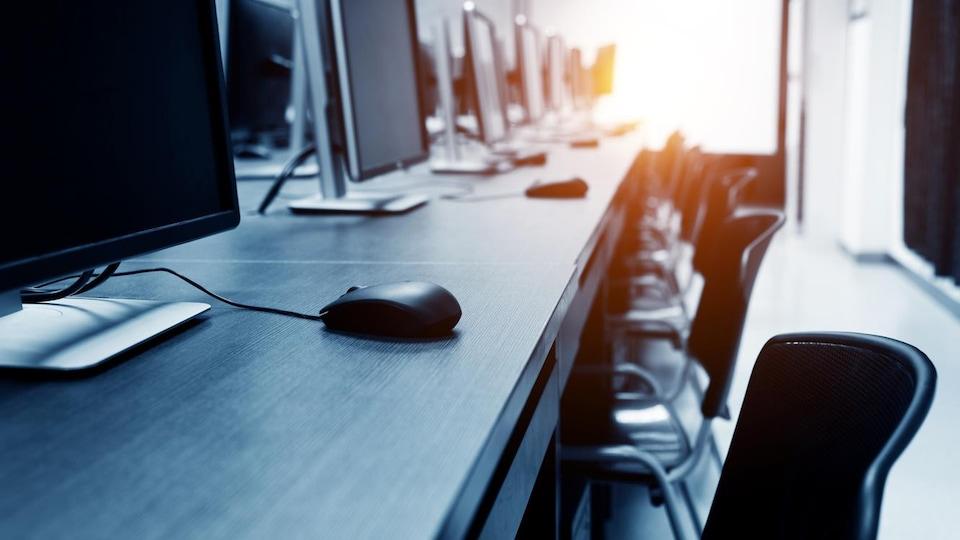Des ordinateurs posés sur des bureaux.