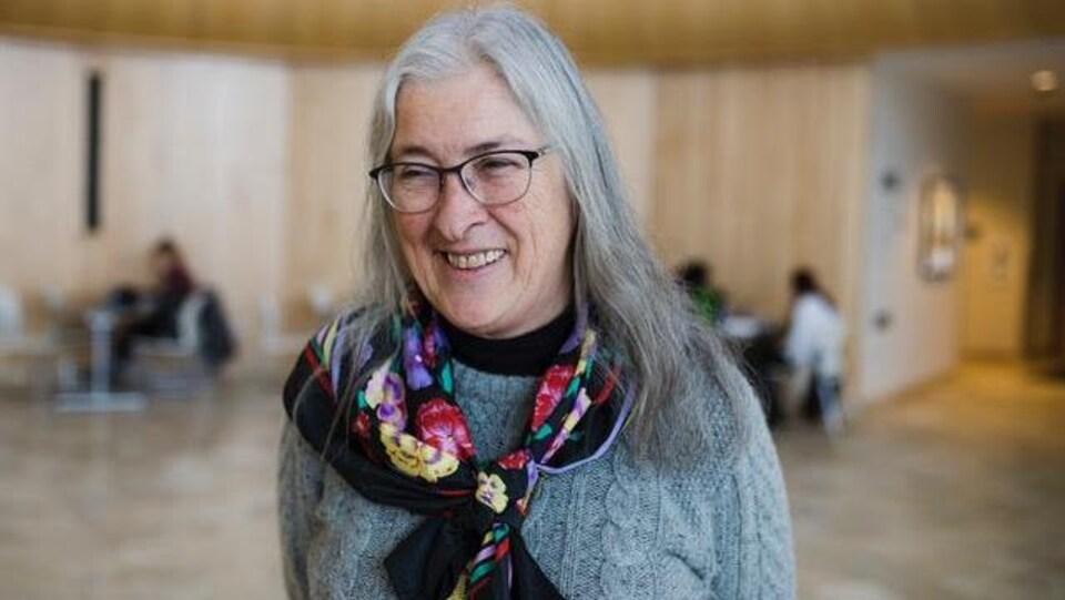 Une femme porte un pull en laine et un foulard autour du cou. Elle sourit à la caméra.