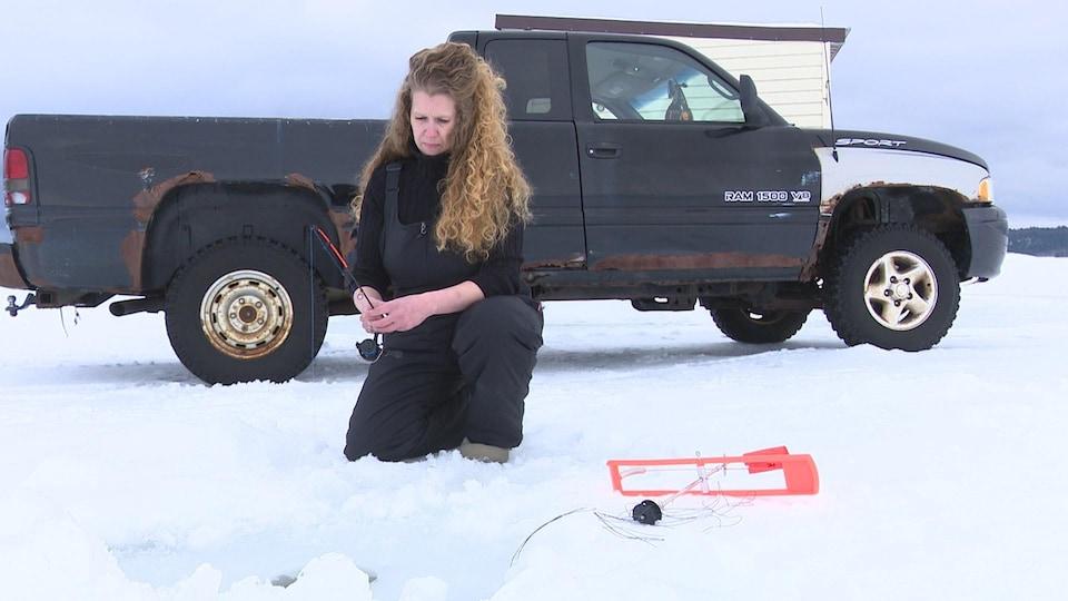Une femme aux longs cheveux frisés pêche sur la glace devant une vieille camionnette.