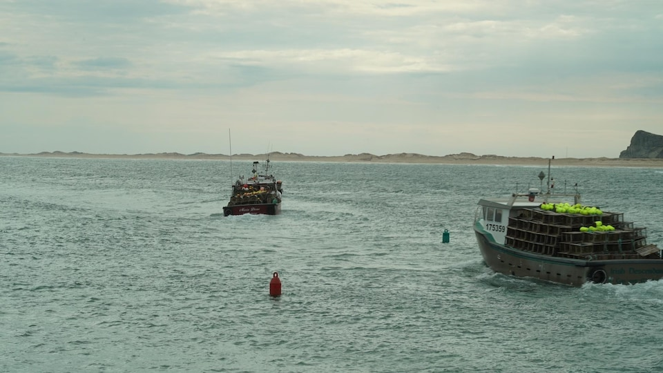 Deux bateaux avancent sur l'eau, dans l'étroit passage désigné par une bouée rouge et une bouée verte.