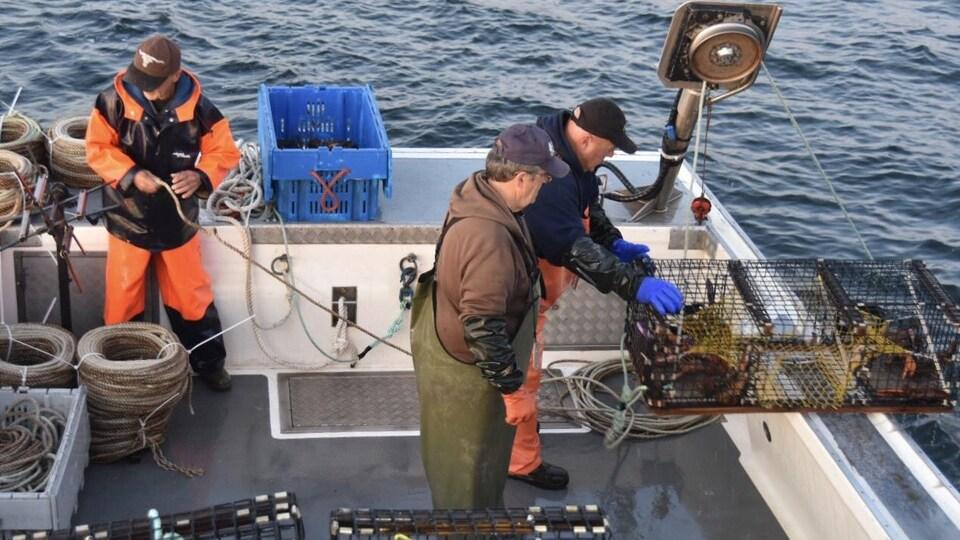 Des pêcheurs qui travaillent sur un bateau en mer.