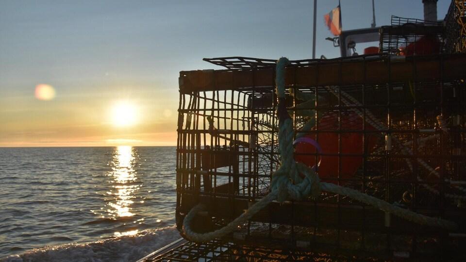 Le soleil se lève sur la mer et un bateau sur lequel sont empilés plusieurs casiers de pêche au homard.