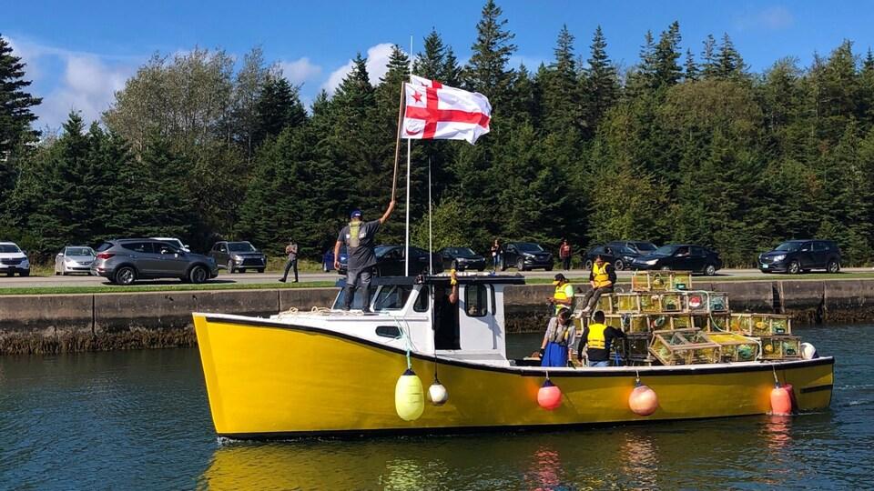 Le drapeau mi'kmaw flotte sur un petit bateau de pêche jaune qui quite le quai.