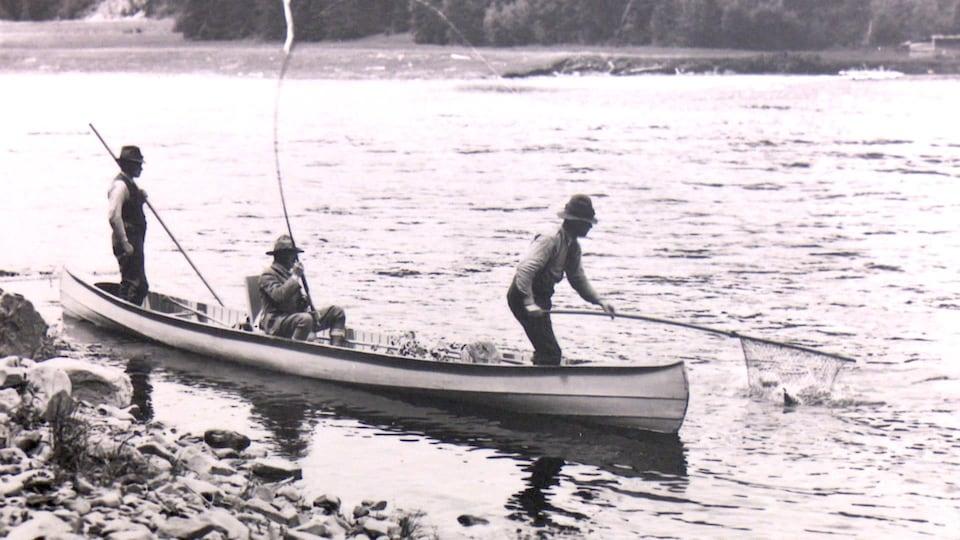 Trois pêcheurs au saumon dans un canot.