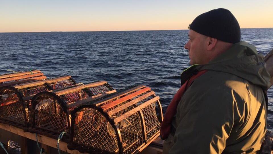 Un pêcheur en mer avec des casiers de homard