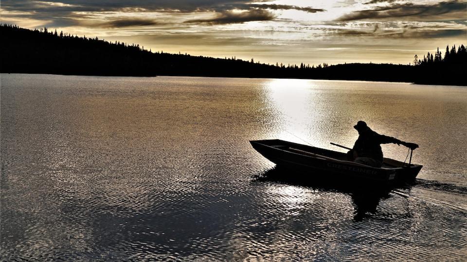 Sur un lac doré, un pêcheur navigue en chaloupe.