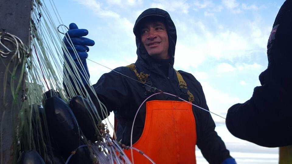Gros plan sur un pêcheur en combinaison de travail sur un bateau