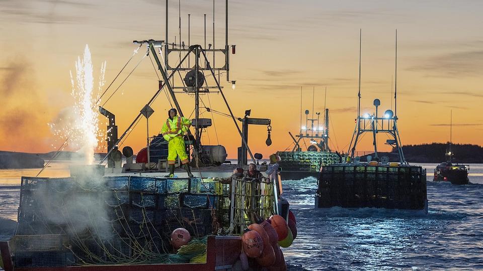 Un homme debout sur un bateau plein de casiers à homard. Un feu d'artifice est lancé à partir du bateau.