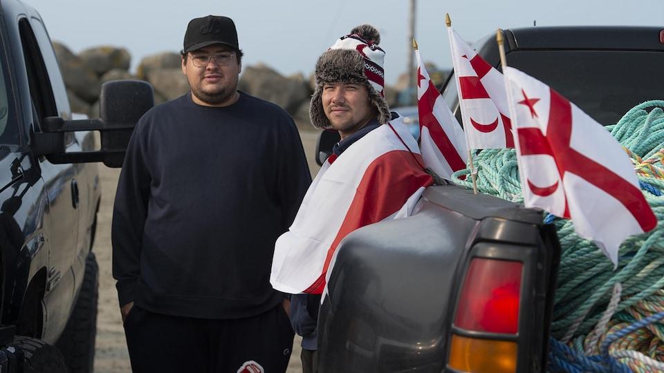 Deux hommes près d'une camionnette décorée de drapeaux mi'kmaq.